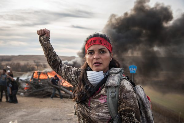"Field Medic wearing camo and a red headband that reads: ""Water is Life,"" raising her right fist. A large wood fire behind her blocks a road. Fellow Water Protectors behind her also have fists raised."
